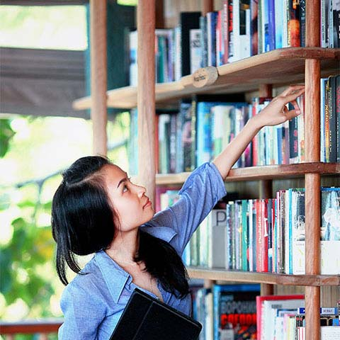 a girl stretching to grab a book from a bookshelf